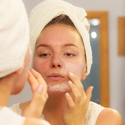 Woman applying primer on combination skin