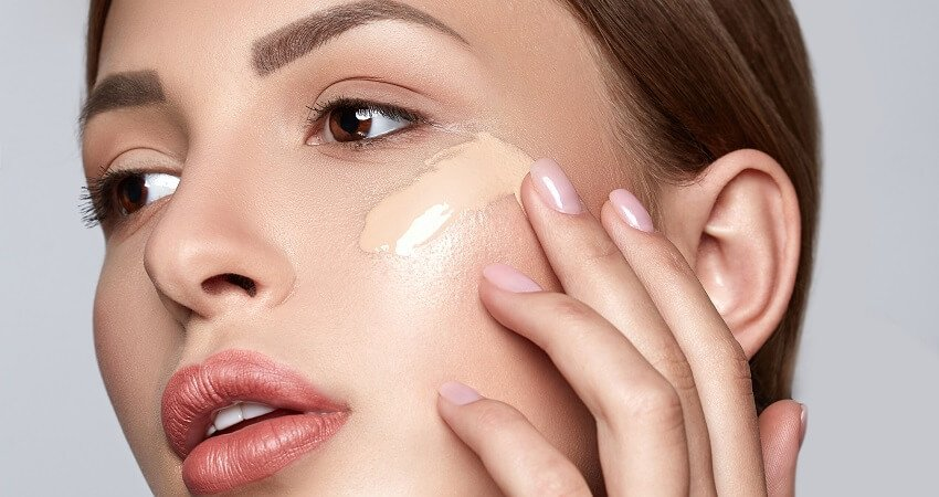 woman applying water based foundation